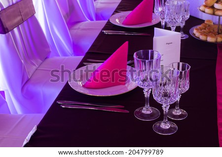 an image of tables setting at a luxury wedding hall - purple lights - stock photo