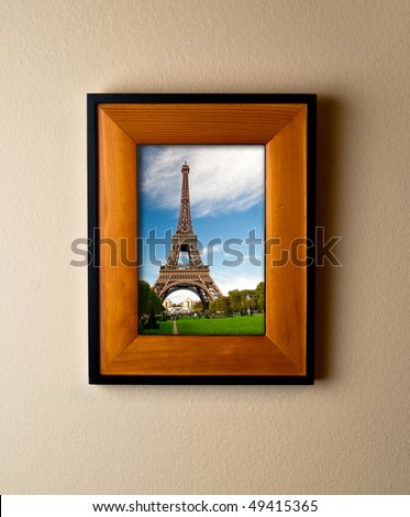 An image of the iconic Eiffel Tower in Paris, France. Presented in a simple wooden frame and hung on the wall as a souvenir. - stock photo