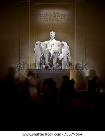 An image of the Lincoln Memorial taken at night.  Tourist move and gather around the monument. - stock photo
