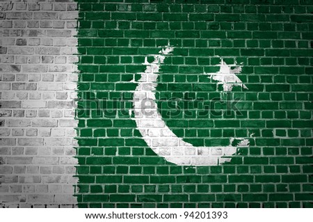 An image of the Pakistan flag painted on a brick wall in an urban location - stock photo
