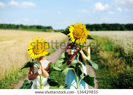 An image of two girls hiding behind sunflowers - stock photo