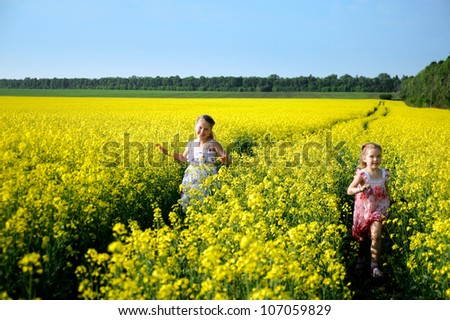 An image of two girls running in the field - stock photo