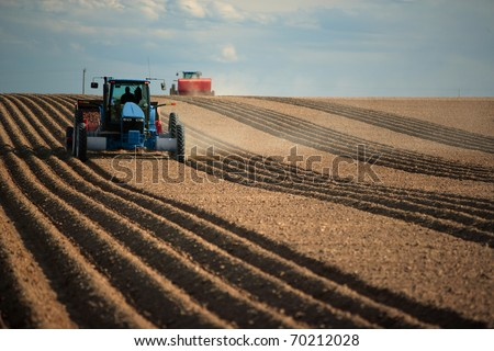 An image of two Tractors planting potatoes in the fertile farm fields of idaho. - stock photo