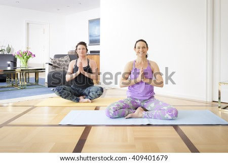 An image of two women doing yoga at home - stock photo