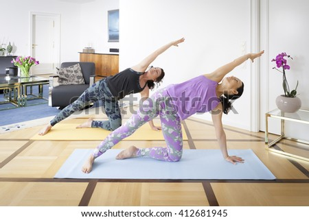 An image of two women doing yoga at home Vasisthasana pose