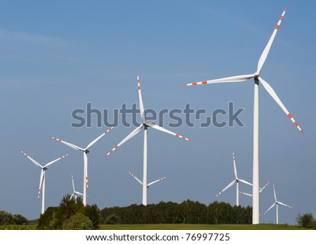 An image of wind turbine against blue sky
