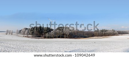 An image of winter scenery with windturbines in the background - stock photo