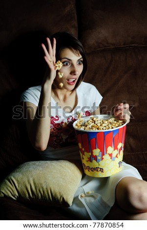 An image of woman watching TV with popcorn - stock photo
