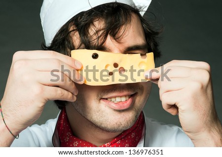 An image of young cook with piece of cheese - stock photo
