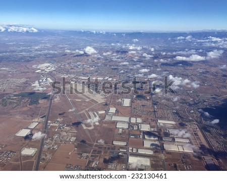 An image shot from an airplane shows a small landing strip surrounded by industrial buildings and residential tracts of homes.  - stock photo