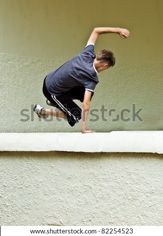 an image with intentional motion blur of a young male doing parkour / free running tricks or tricking