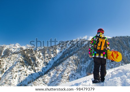 An image with snowboarder with a helmet and glasses on the background of high snow-capped Alps in Grindelwald, Swiss