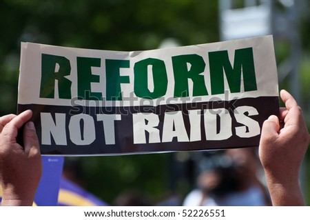 "An immigration activists holds a sign saying, ""Reform, Not Raids"" during a protest rally."