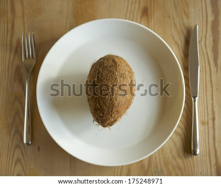 An impossible task. A coconut on a white dinner plate with cutlery on the sides.