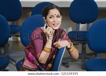 An Indian business woman communicating on cell phone in training room - stock photo