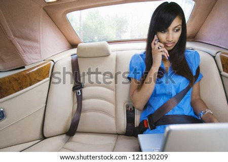 An Indian business woman using laptop while communicating on mobile phone in car - stock photo