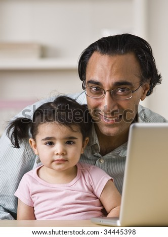 An Indian father holds his young daughter.  He is smiling directly at the camera. There is a laptop on the table. Vertically framed shot.