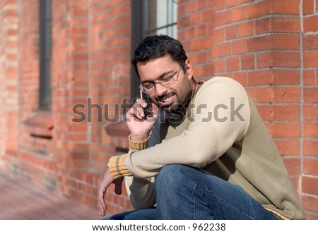 an indian man talking on a cell phone. - stock photo