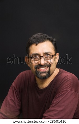 An Indian man with a beard against a black background - stock photo