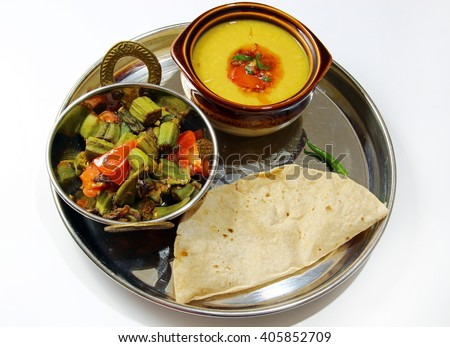 An Indian platter of Bhindi masala, Chapati, arhar lentil daal isolated on white background.