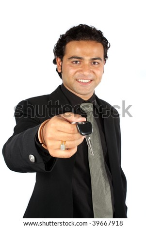 An Indian sales executive handing over the keys of a car to a customer, on white studio background. Focus on keys. - stock photo