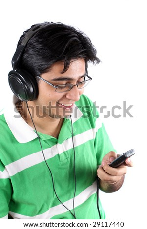 An Indian teenage boy in a green t-shirt, listening to music on his MP3 player, on a white background. - stock photo