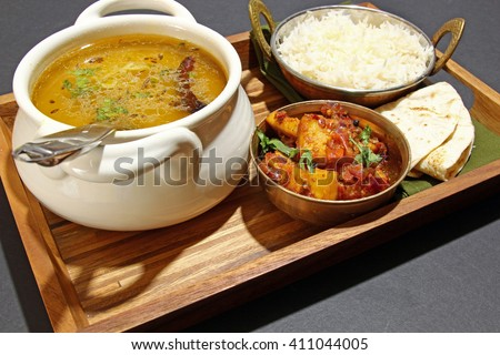 An Indian vegetarian meal comprising of yellow lentil daal or soup with Karahi paneer, rice and chapati on a tray.