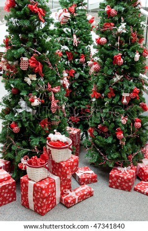 An indoor Christmas display with decorated trees and packages. - stock photo