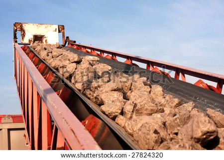 An industrial conveyer system loading rock into a truck - stock photo