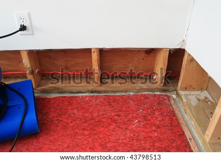 an industrial fan drying water damaged wall and carpet padding in a residential basement - stock photo