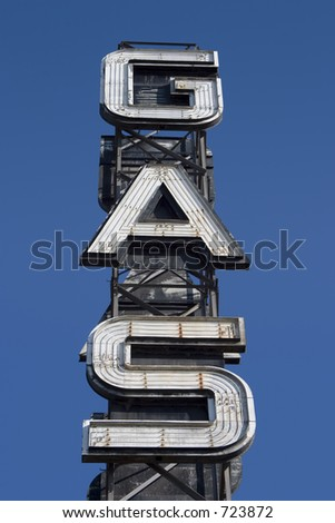 An industrial looking sign for a gas station against the blue sky.