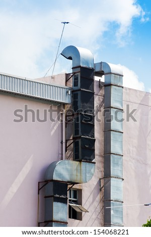An Industrial metal exhaust vent outlet attached to a wall - stock photo