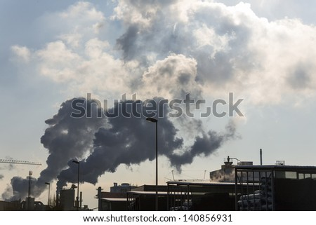 an industrial plant chimney with smoke. symbolic photo for environmental protection and ozone. - stock photo