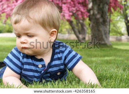 An infant boy learns to explore on the grass outside.