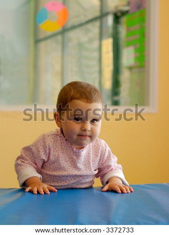 An infant girl in a gym - a lot of determination in her face. - stock photo