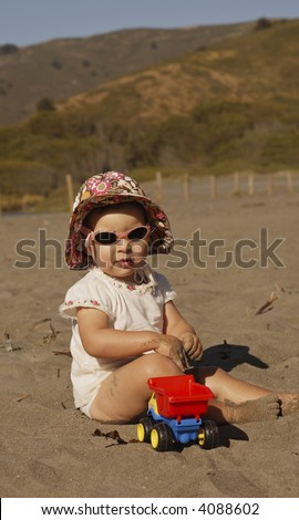 An infant girl in sunglasses lit by the late afternoon sun plays in the sand with a toy truck. - stock photo