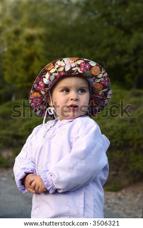 An infant girl is standing straight on a cold summer evening in a colorful hat. - stock photo