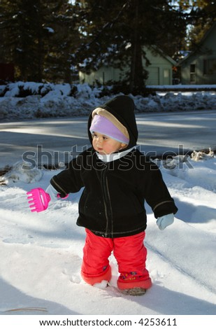 An infant girl with a toy rake standing in the snow. - stock photo