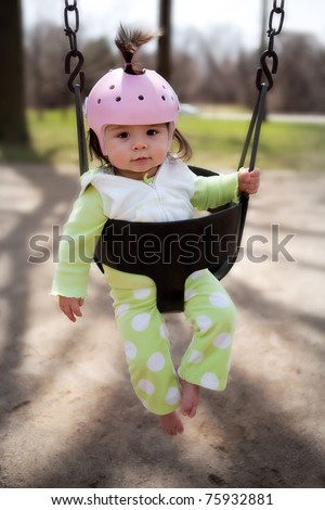 An infant in a playground swing with a protective helmet - stock photo