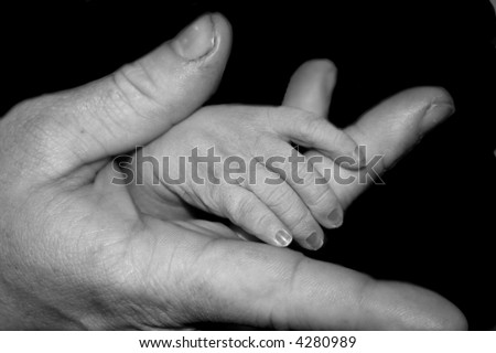 An infant's fingers in daddy's hand. - stock photo