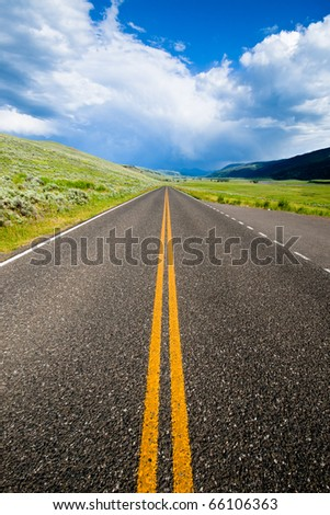 An infinite road through the Lamar Valley in Yellowstone National Park - stock photo