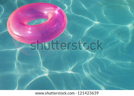 An inflatable tube floating on water in swimming pool - stock photo