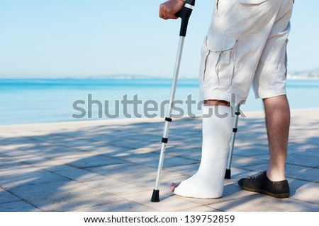 An Injured man with a plaster on the beach - stock photo