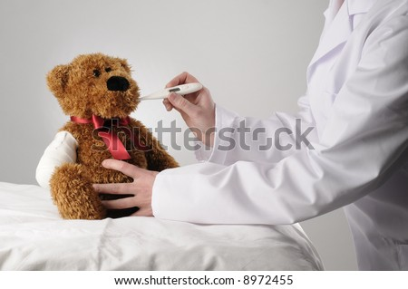 an injured teddy bear having a examination by a pediatrician - stock photo