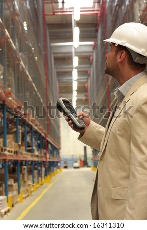 An inspector with scanner in a factory maintaining stocks of finished products on the shelves in a storeroom. - stock photo