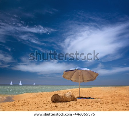An installed beach umbrella at the beach of the Black Sea over beautiful sea scape with yachts in Odessa region in Ukraine - stock photo
