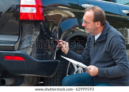 An insurance expert. Case of damage to the car. Car Insurance - stock photo