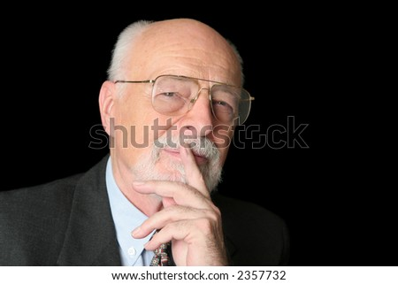 An intelligent senior man with a thoughtful expression over a black background. - stock photo