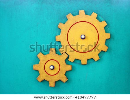 An interconnected rotating cogwheels on a blue wall for the concept of industrialization.