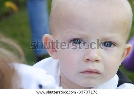 An interested little boy with big blue eyes and a bald head